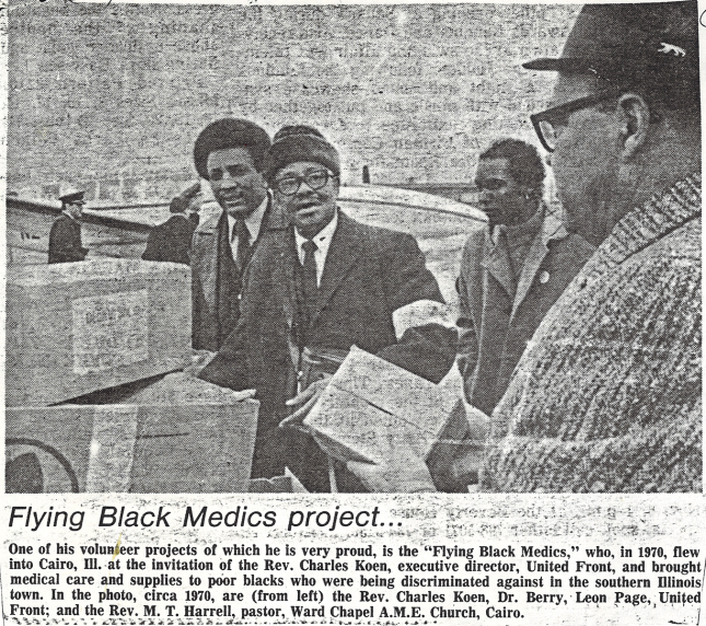 a newspaper clipping with photograph and caption showing 4 black men on an airstrip with boxes.