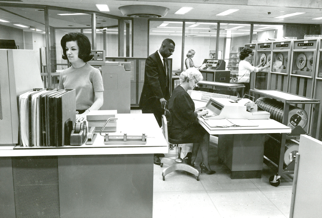 A man watches a woman working on a keyboard while other women work with macnines and reel to reel systems.