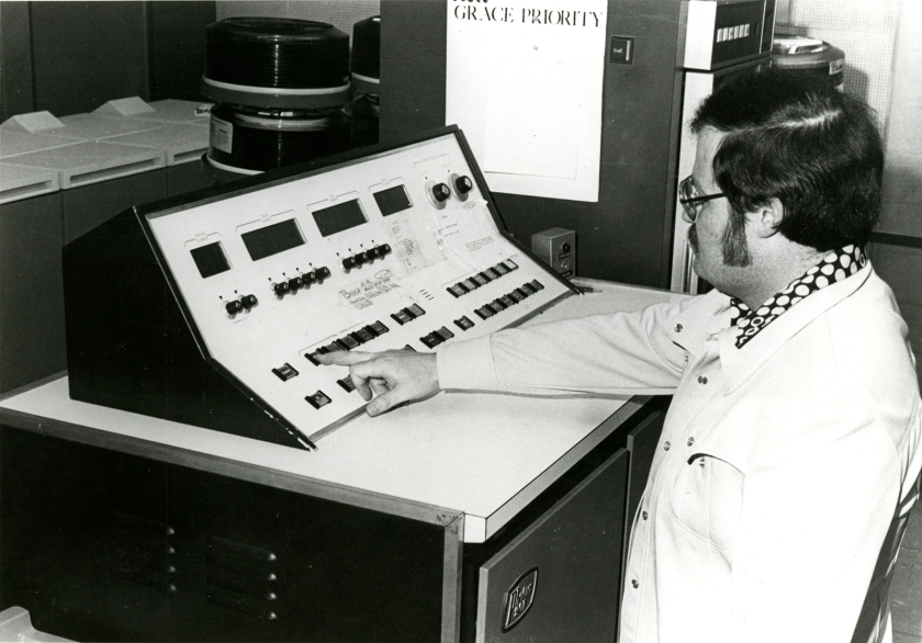 A man in a white coat presses a button on a control panel.