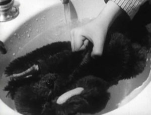 A teddy bear being held under watter in a sink.
