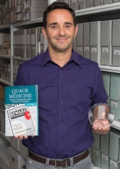 Eric Boyle stands in an archival storage room holding his book and an award.