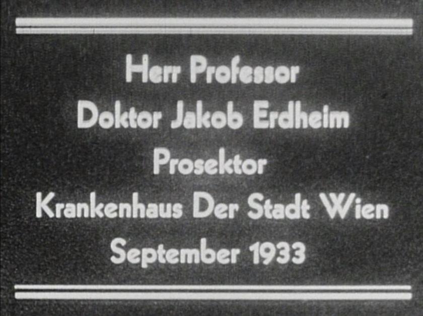 Grainy still from film that reads: Herr Professor Doktor Jakob Erdheim Prosektor Krankenhaus Der Stadt Wien September 1933