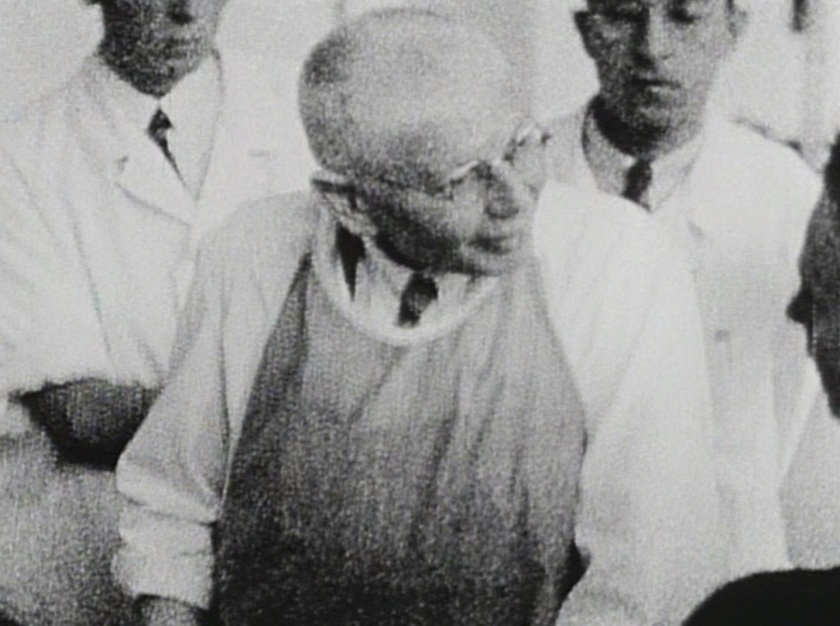 A grainy still showing an older man in glasses and a shirt and tie with an apron over them leaning over and talking to someone offscreen. Younger men stand behind him.