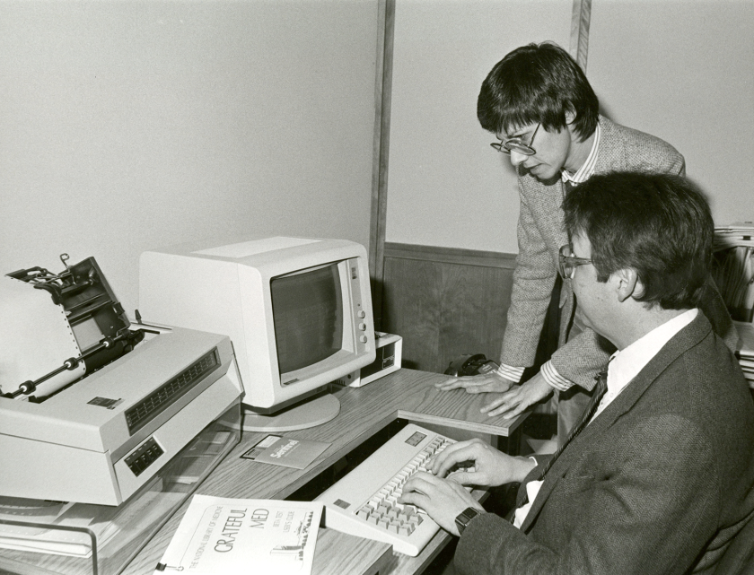 A man uses a keyboard while a woman leans next to him, they look at a CRT monitor, a dot matrix printer is on the desk.
