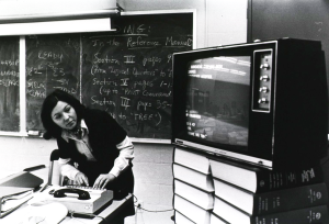 A television is sitting on top of two stacks of books; a woman looks at the TV while typing on a dial-up modem and keyboard.