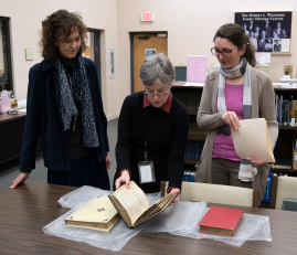 Three women inspect three books on bubblewrap on a table.