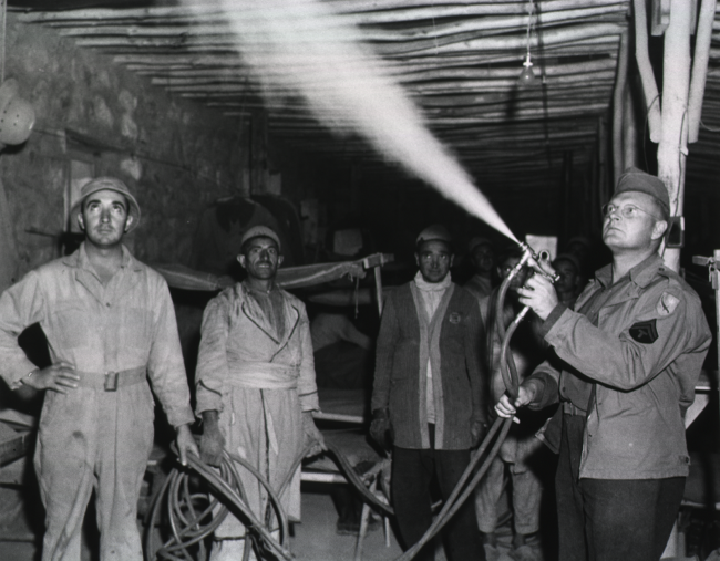 Men in usiform watch as one sprays the inside of a building.