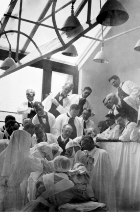 In a skylit room about twenty men in white coats crane to observe surgeons and nurses working.
