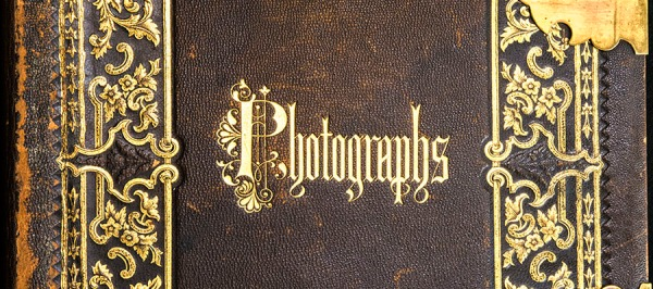 A gold embossed leather cover with brass clasps titled Photographs.