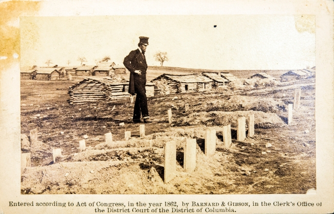 A tall man in a tall hat and dark suit of clothes stands looking at a line of new graves, low log structures in the background.