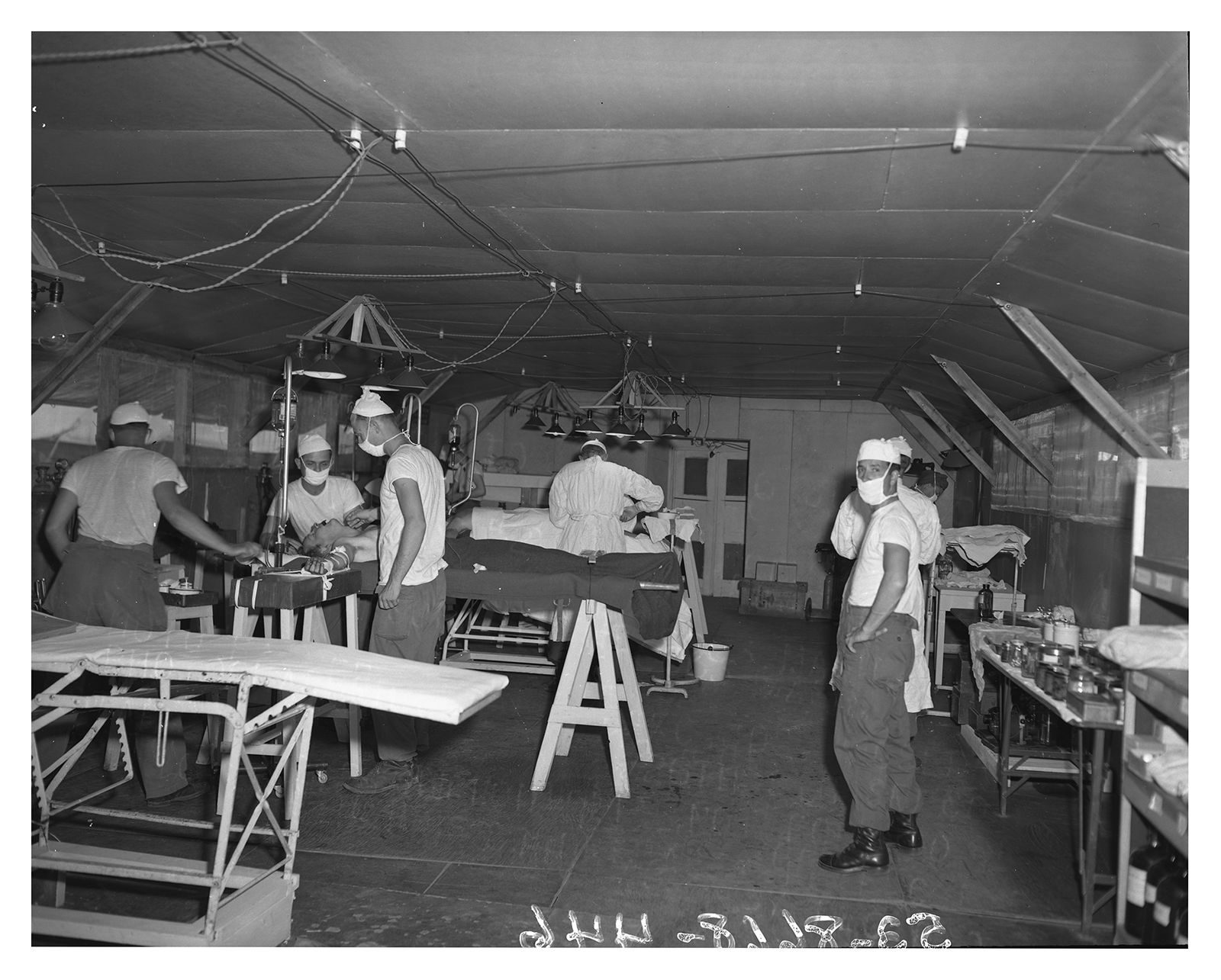 An operating tent where military surgions are working on two patients. & MASH units were conceived and developed by DeBakey and the ...