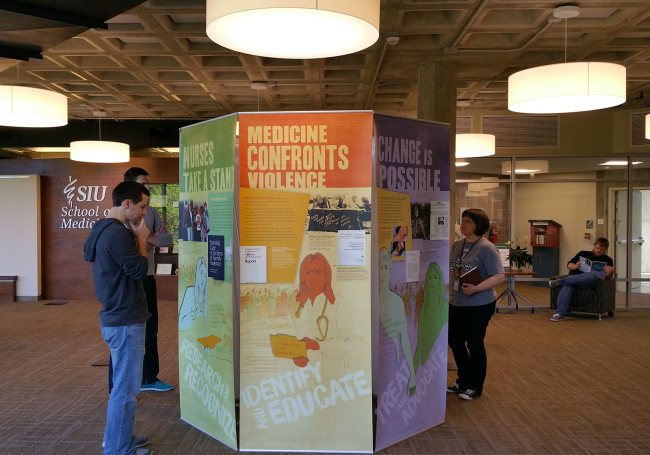 Young people stand looking at 6 banners set up in a hexagonal column in a library setting.
