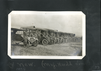 Eight canvas topped vehicles lined up wih soldiers standing next to them.