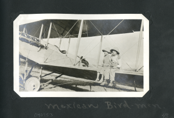 Two yound children in straw hats sit on the lower wing of a biplane.