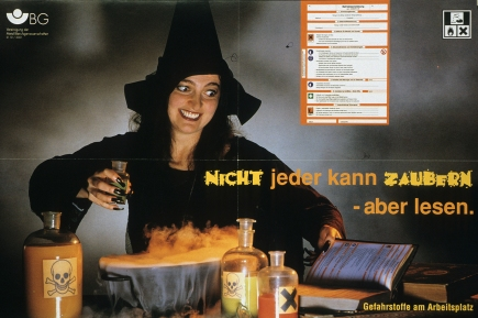 "A woman dressed as a witch is mixing a smoking concoction in a large pot. Bottles are filled with orange and yellow liquids, and bare either a skull and crossbones or a large black ""X"" indicating poison. A book is open beside her, and an enlarged version of the page she's reading appears above her head"