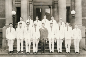 Fifteen young men in suits pose on the steps of a large building.