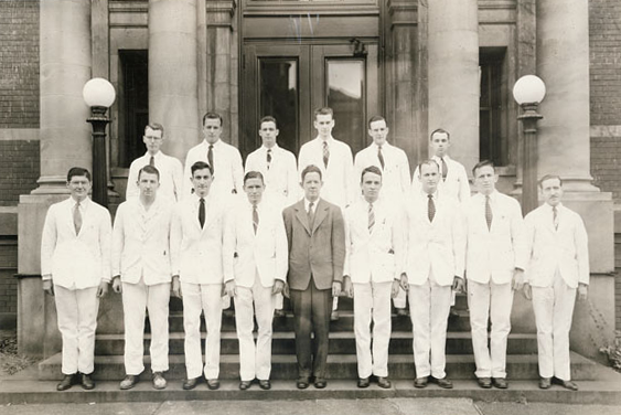 1945 class photo of 15 young men in suits on the steps of a building.