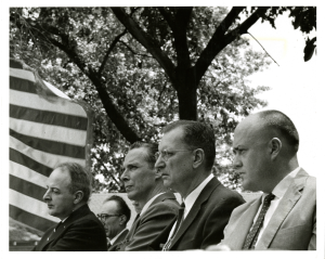 A group of men in suits sit outdoors under an American flag.