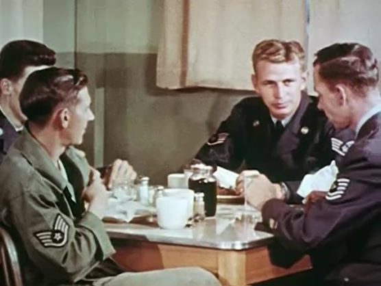 Four men in uniform sit around a table eating.