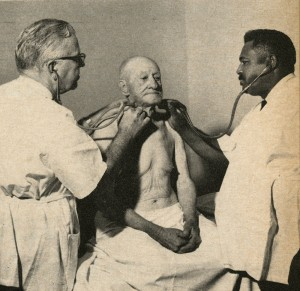 Two men with stethescopes examine a shirtless man.