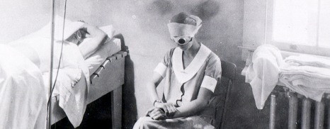 A nurse in dark goggles sits by a patient lying with skin exposed to a bright electric light.