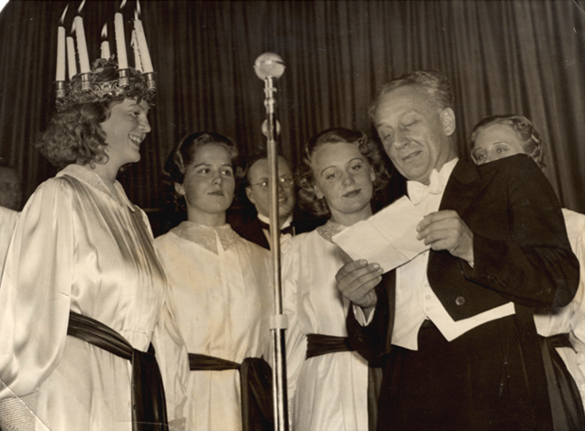 A man in evening dress surrounded by young women in white dresses, one of which wears a crown of candles, reads form a paper in front of a microphone.