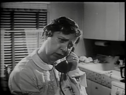 A distressed woman on the phone in her kitchen.