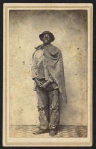 A full length portrait of a black man in layered ragged clothes.