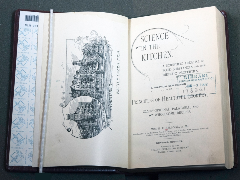 A book open to the title page Science in the Kitchen and Frontispiece illustration of a Sanatarium in Battle Creek, Michigan.