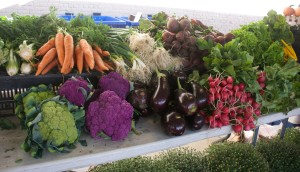 A variety of flowers and vegetables at a farm market.