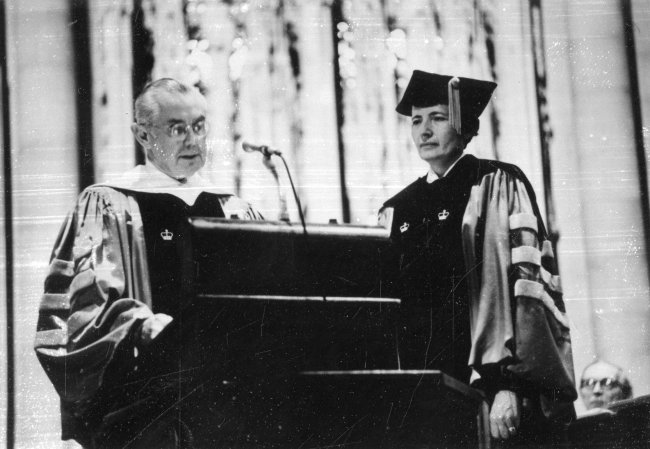 A woman in academic robes stands next to a man in academic robes speaking at a podium.