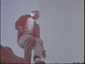 A boy stands on the edge of a cliff.