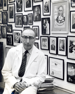 DeBakey in a lab coat poses in front of a wall covered with framed photgraphs and awards.