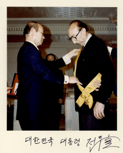 A man adjusts a yellow sash over DeBakey's suit.