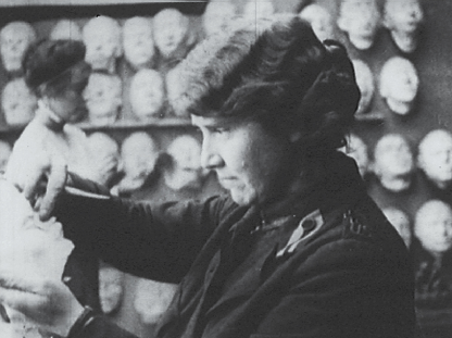 A woman looks carefully at a prosthetic in progress.