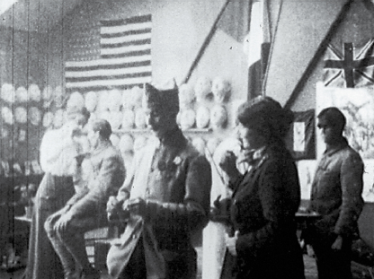In a studio hung with flags and masks soldiers consult the artists.