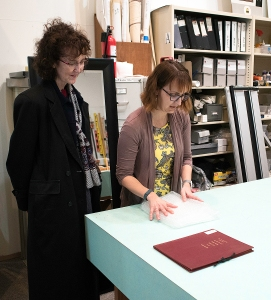 Two women look at a book on a table in a workspace.