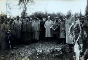 A grou of men gathered around a grave with flowers while a preacher speaks.