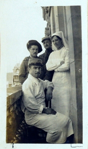 Three men and a nurse pose on a balcony.