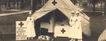 Three nurses and a dog pose wear white with the red cross symbol outside a red cross tent.