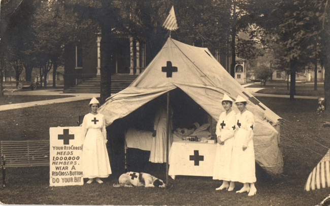 Postcard featuring a photograph of 3 Red Cross nurses standing in front of a Red Cross tent.