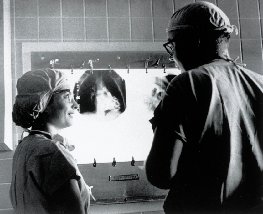 A man and a woman in scrubs talk in front of an x-ray lightboard.