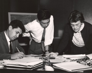 Three people pore over documents on a table.
