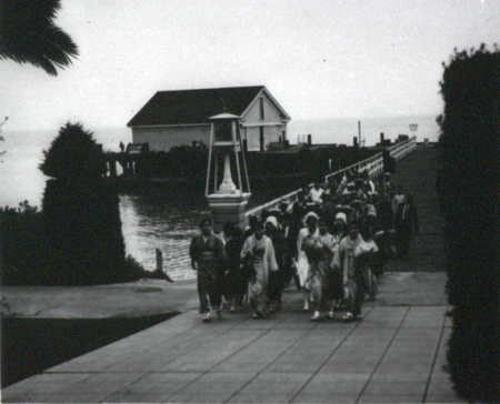 A group of people walk off a dock.