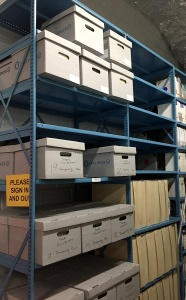 Archival boxes stacked on metal shelves.