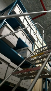 A metal ladder leads up to high shelves stacked with boxes.