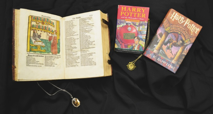 Photograph of one opened book, two closed books, and two pendant necklaces.