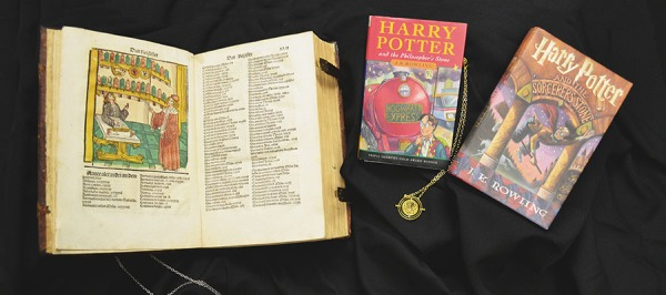 Photograph of one opened 16th century book, two closed Harry Potter novels, and two pendant necklaces.