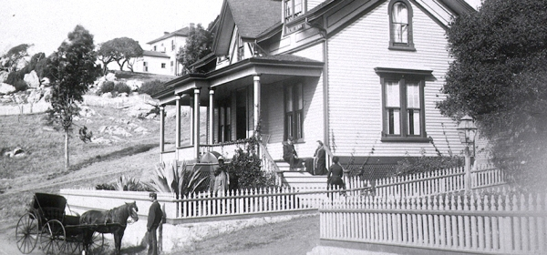 In a hilly landscape, men and women around a large frame house with a long porch, a horse and carriage wait in front.