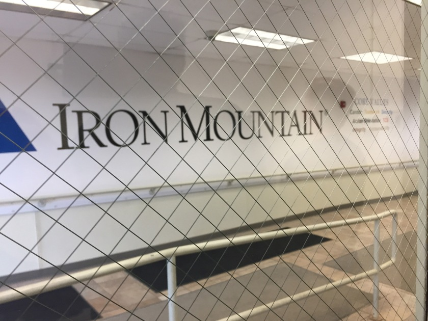 Iron Mountan printed along a hallway wall, seen through a glass door.